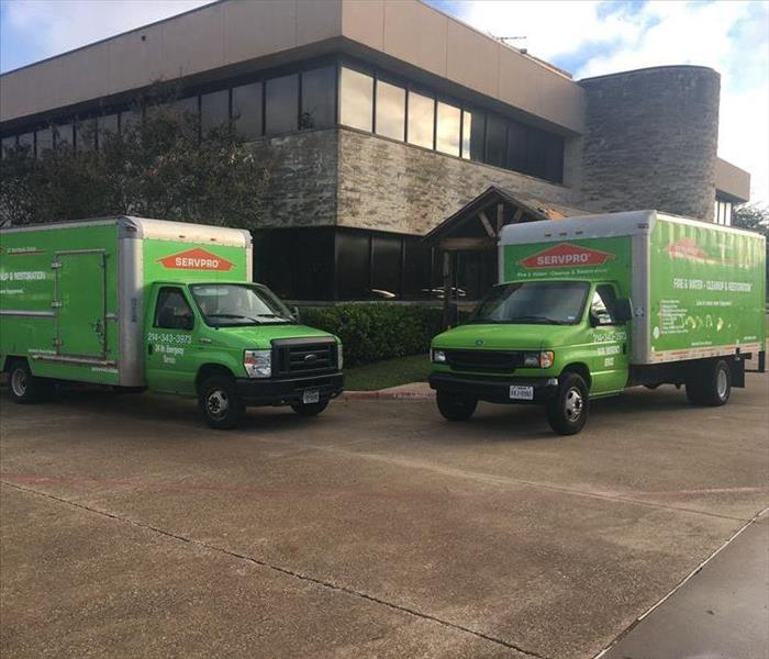2 SERVPRO trucks parked outside structure.