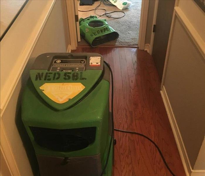 Dehumidifier and air movers in a hallway.