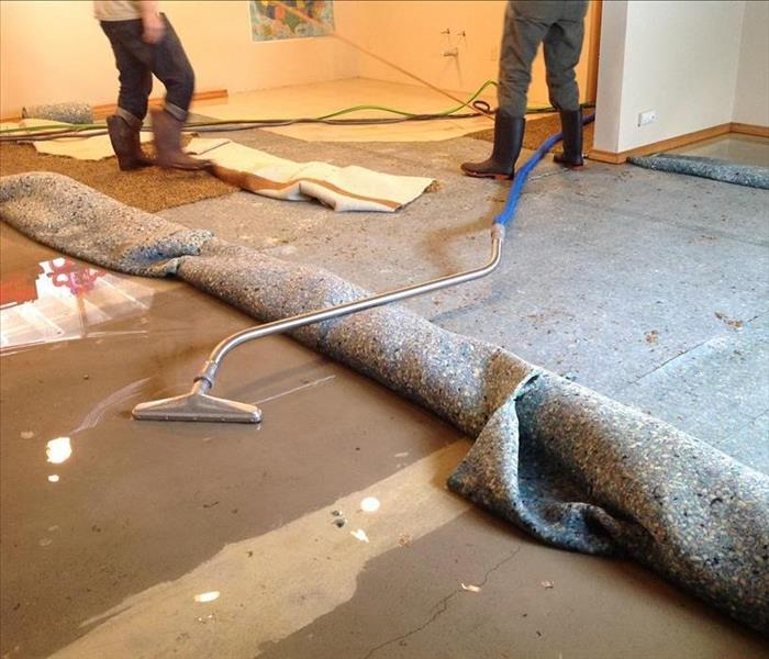 A rolled carpet and someone extracting water from the floor